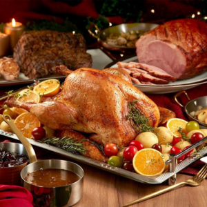 Photo of turkey and hams served with side dishes and sauce.